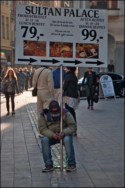 Man med reklamskylt för restaurang.