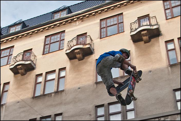 Skateare som hoppar upp bland fönster