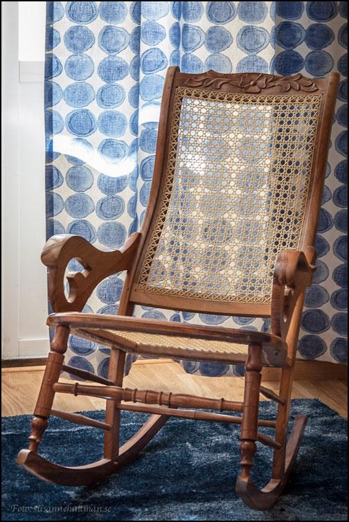 Gungstol på blå matta vid blå gardiner