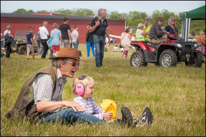 Man och barn sittande på gräs
