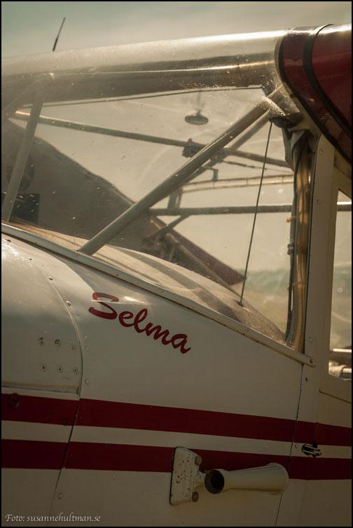 Flygplansfönster med texten Selma