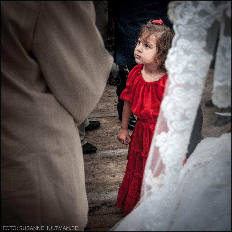 Flicka i röd klänning bakom bruden