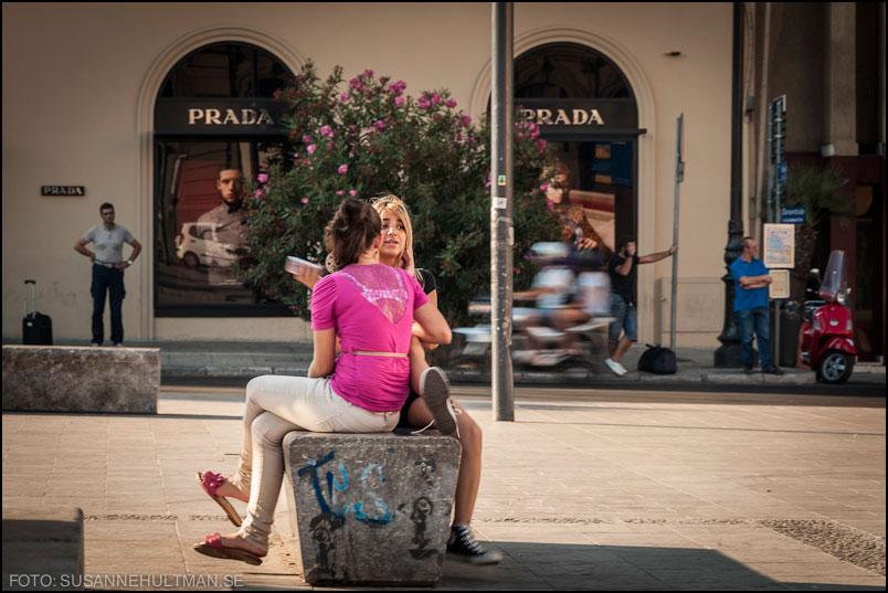 Flickor på bänk vid Prada-fönster