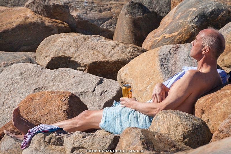 Solbadare som dricker öl