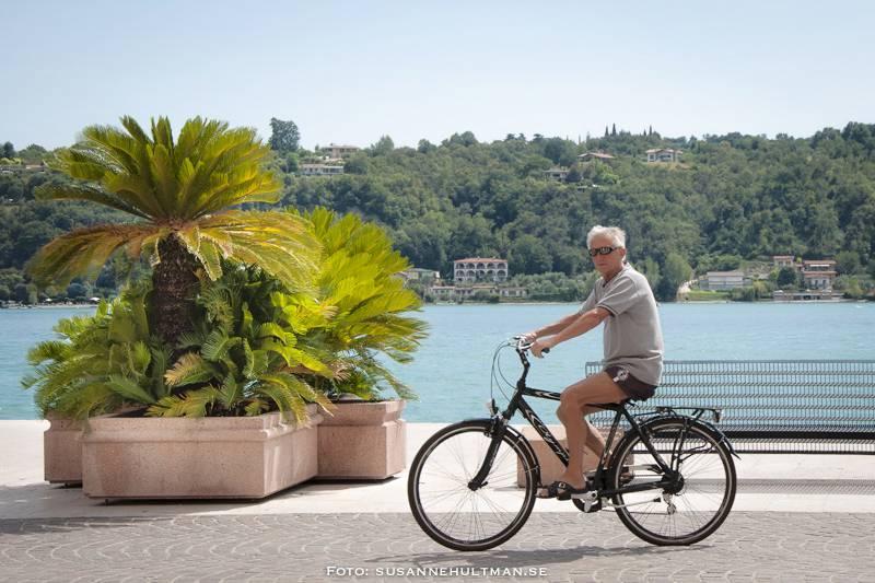 Cyklist med solglasögon vid strandpromenaden i Salò.