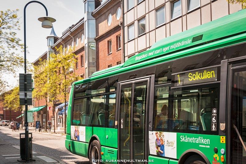 """Grön buss med texten """"Biogas med stans eget miljöbränsle"""" lämnar busshållplatsen"""
