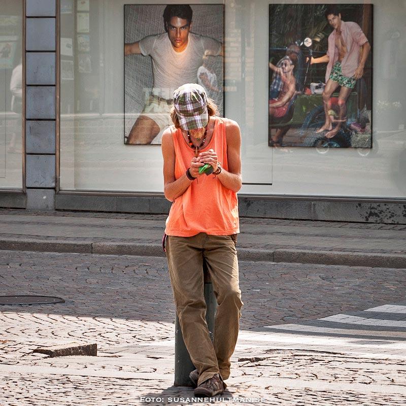 Kille med mobil vid modefoton