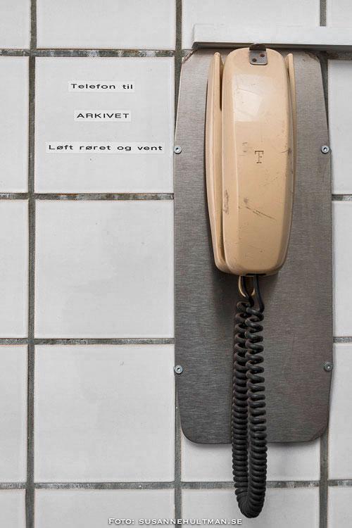 """Gammal telefon med texten """"Telefon til ARKIVET Løft røret og vent"""""""