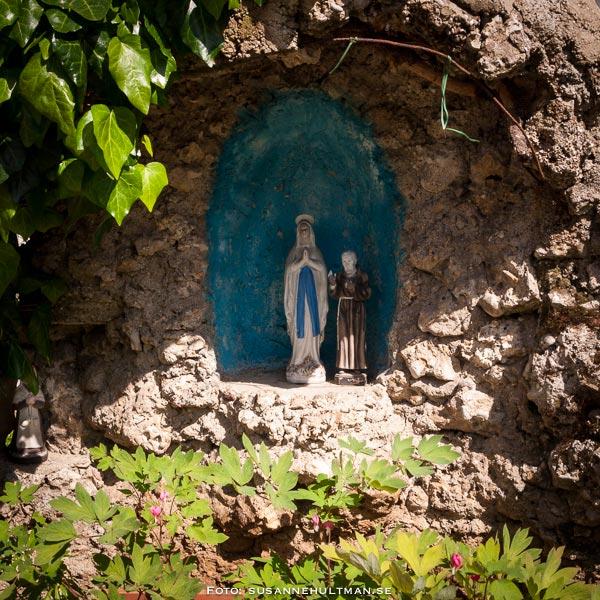 Madonna med sällskap inramad i grotta
