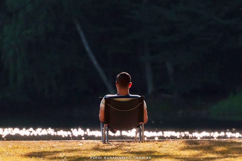 Man i solstol vid vatten