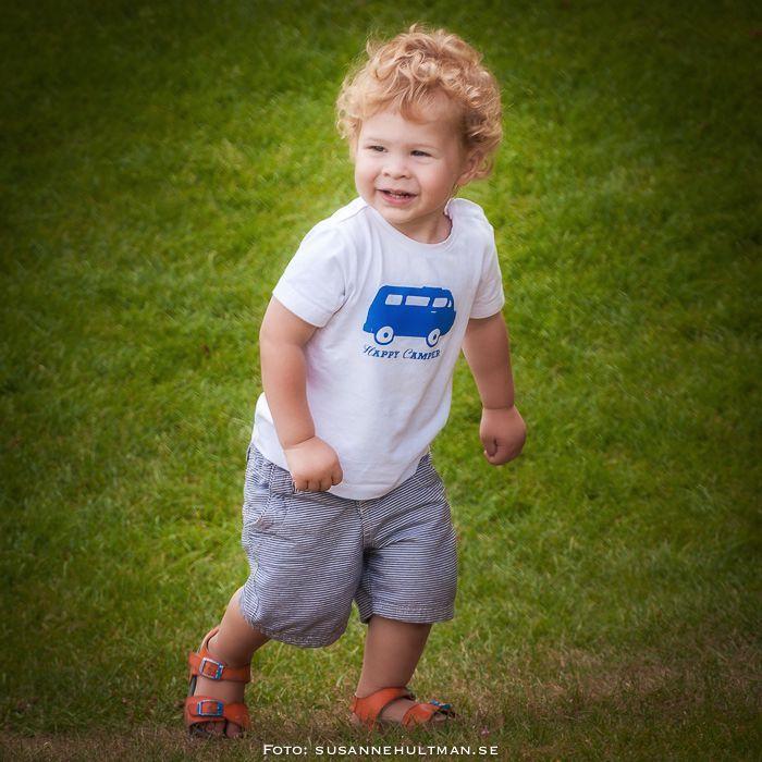 Glad pojke på gräsmatta