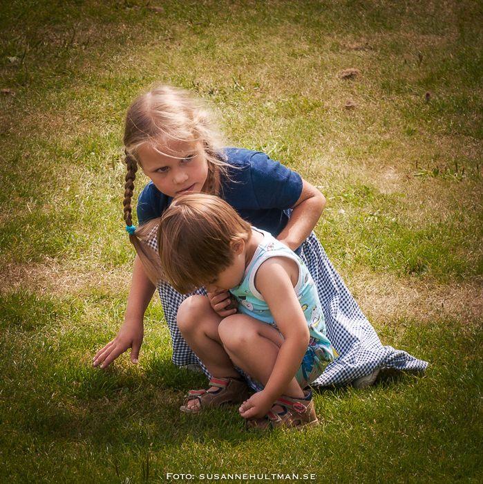 Två barn på knä i gräsmattan
