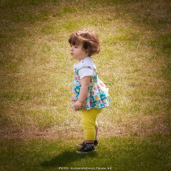 Liten flicka på gräsmatta