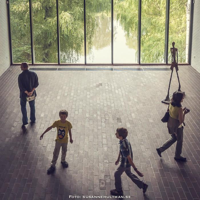 Fyra besökare och en skulptur vid stort fönster