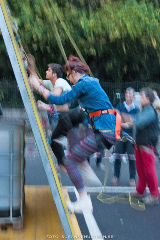 Två ungdomar som klättrar upp på en klättervägg.