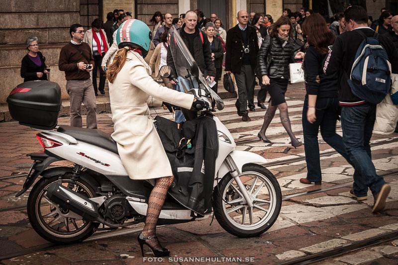 Kvinna som kör vespa i nätstrumpor och högklackat