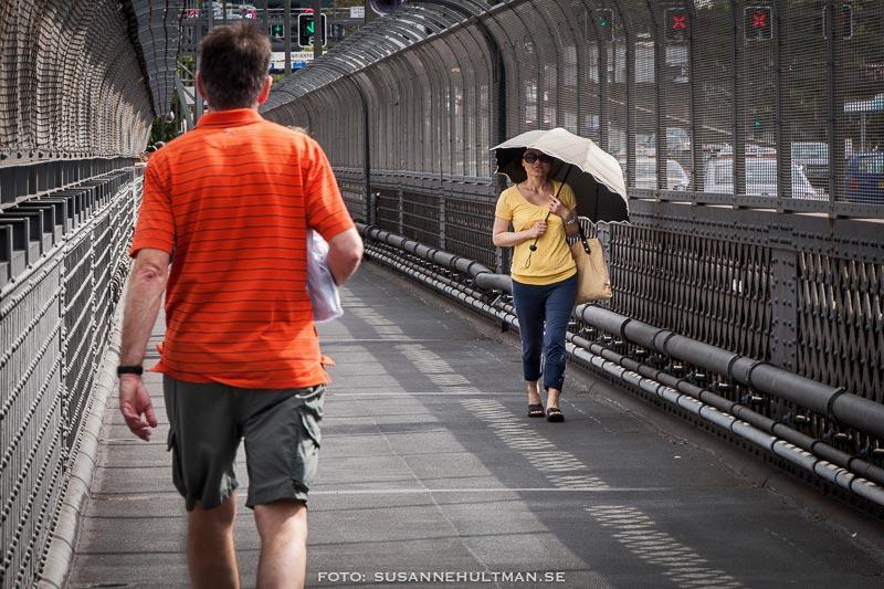 Kvinna med paraply och orange man.