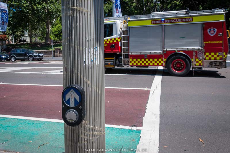Tryckknapp vid övergångsställe och en brandbil