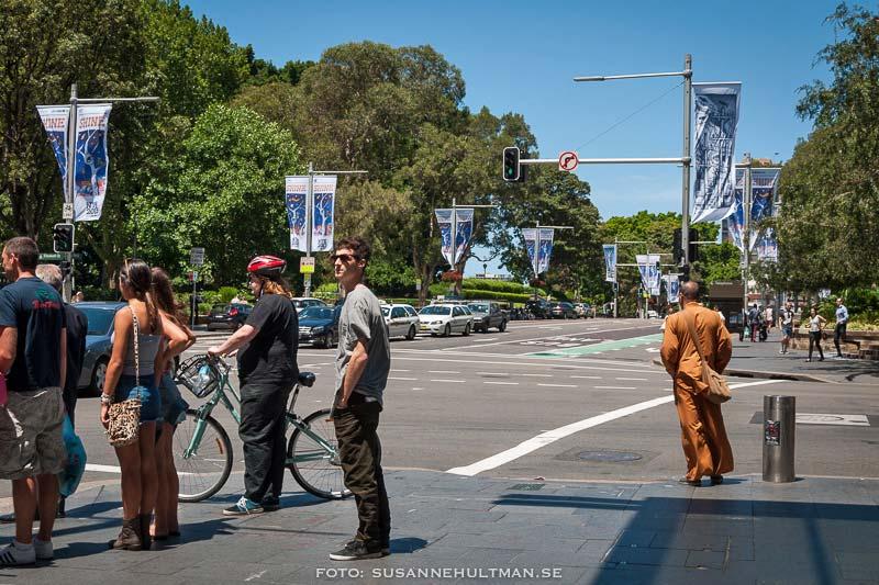 Fotgängare och en cyklist som väntar vid övergångsställe.