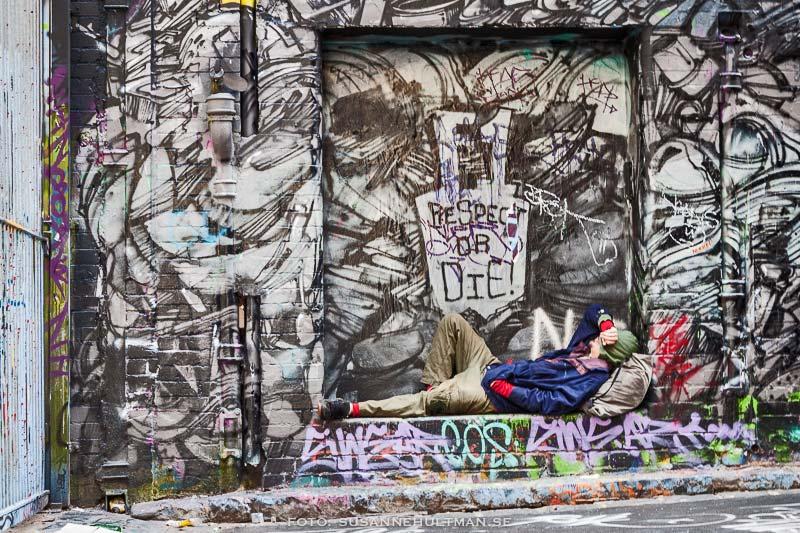 Man i prång omgiven av graffiti