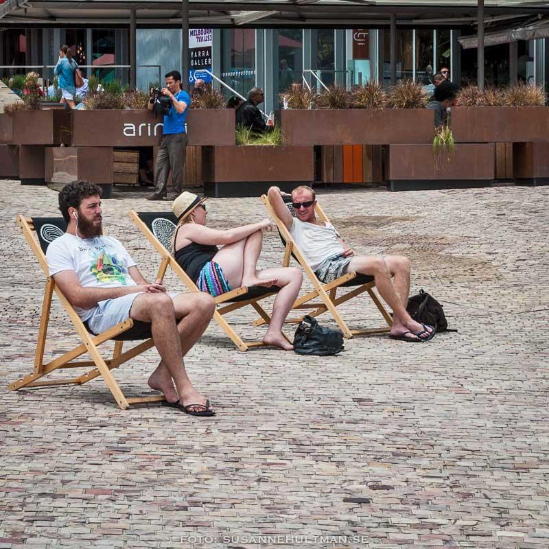 Människor i solstolar på Federation Square