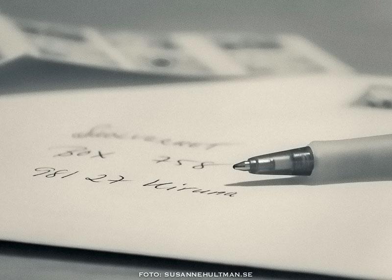 Kuvert med textad adress, frimärken och penna bredvid.