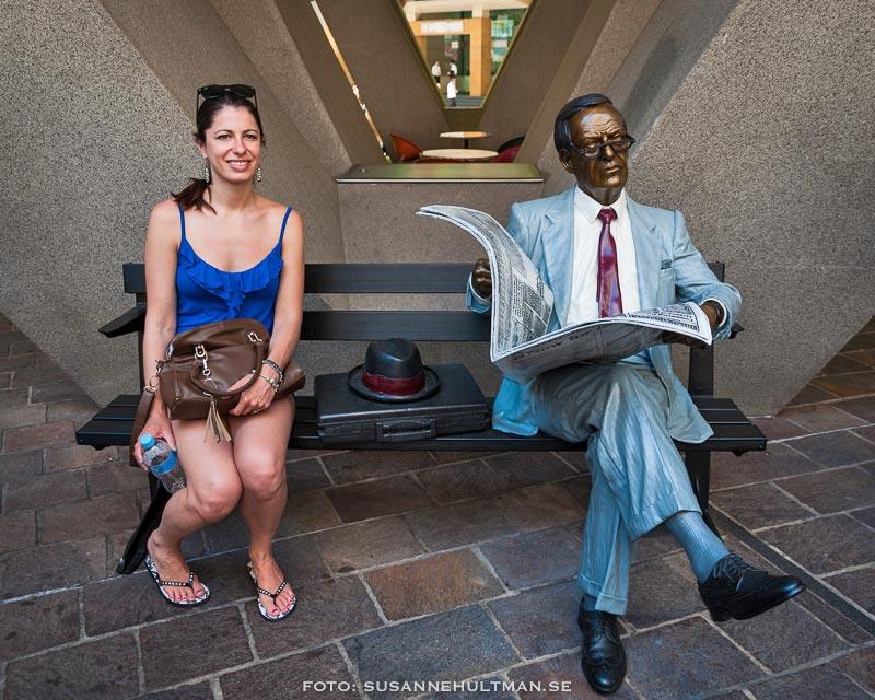 Kvinna på bänk där man läser tidning