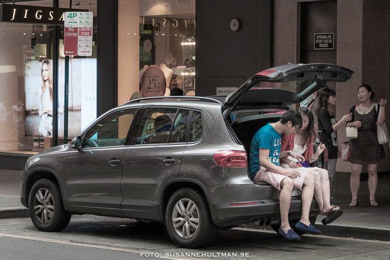Två ungdomar sitter i bagageutrymmet på en bil