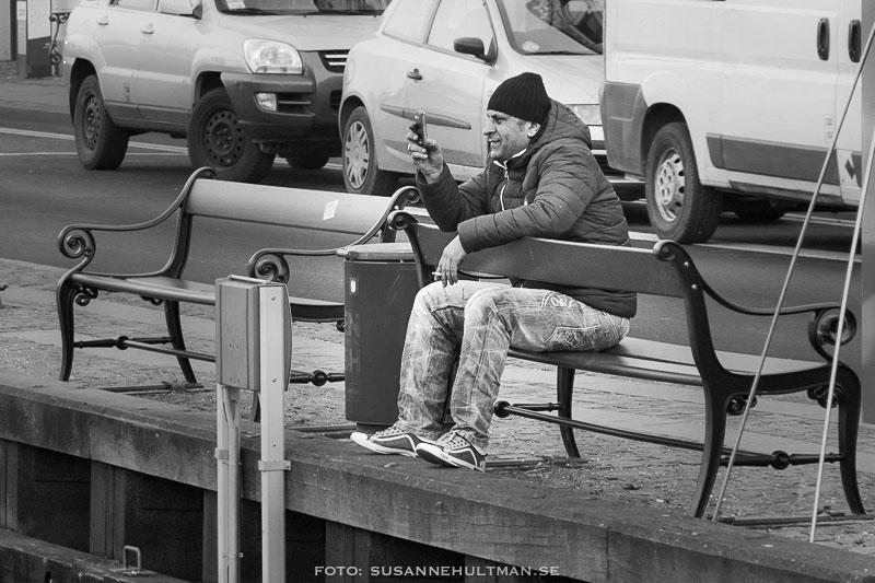 Man som sitter bakvänt på en bänk