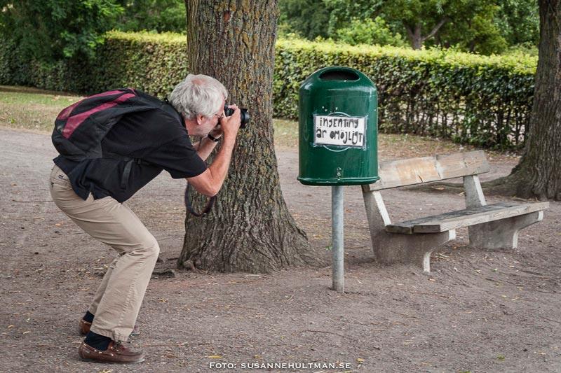 """Fotograf som tar en bild på skylt med texten """"Ingenting är omöjligt"""" - och en bänk"""