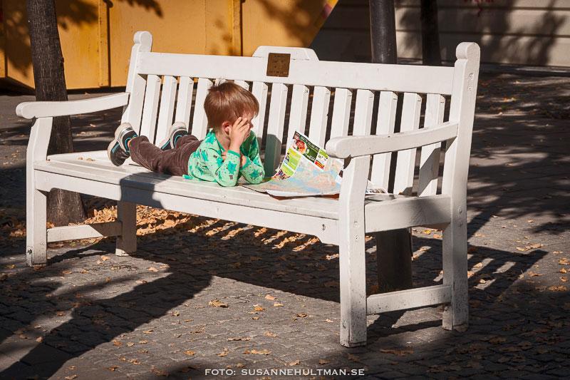 Pojke med karta på bänk