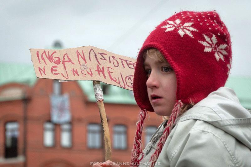 """Flicka med handtextad skylt  med """"Inga nazister. Nej, nej, nej"""""""
