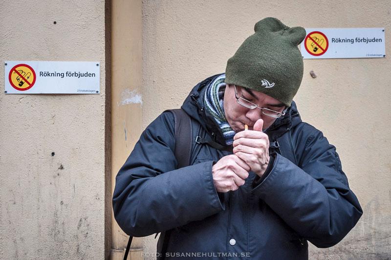 """Man som tänder en cigarrett vid skyltar med """"Rökning förbjuden"""""""