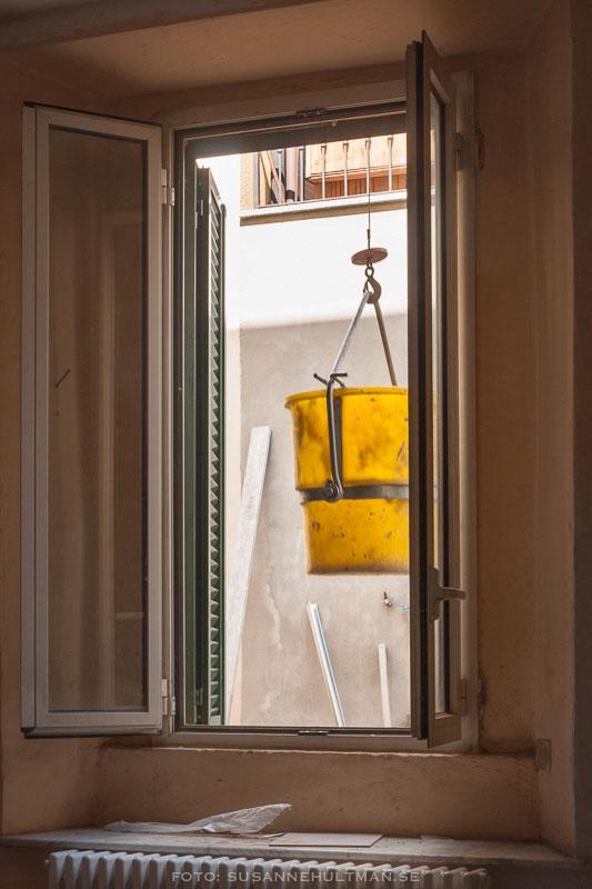Krok med hink vid öppet fönster