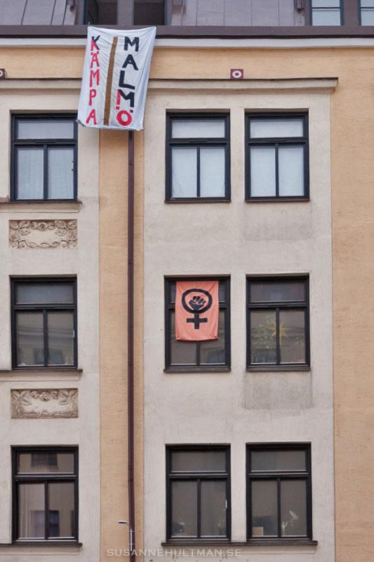 """Fönsterfasad med kvinnomärke och texten """"Kämpa Malmö"""""""