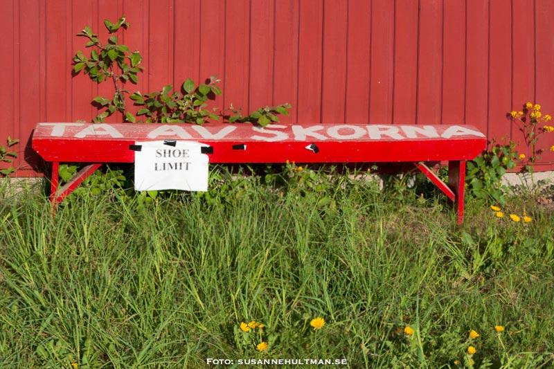 """Röd bänk med texten """"Ta av skorna"""", omgiven av grönt gräs"""