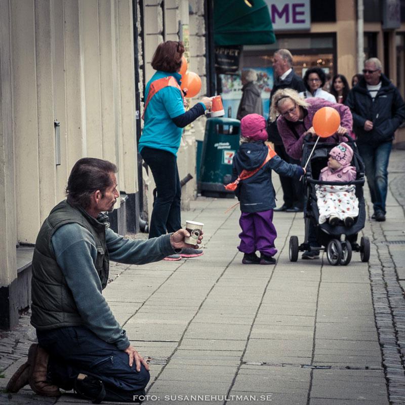 I förgrunden en tiggare på knä och i bakgrunden Amnesty som samlar in pengar