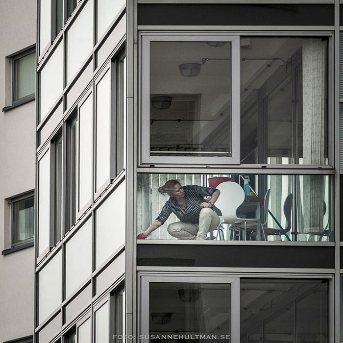Kvinna putsar fönster på en balkong