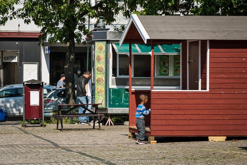 En liten färgad pojke tittar in i SD:s tomma valstuga.