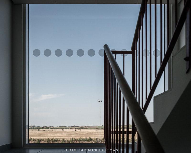 Stort trapphusfönster med en rad vita prickar