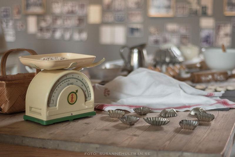Bord med gammal våg, kakformar och mjöl.