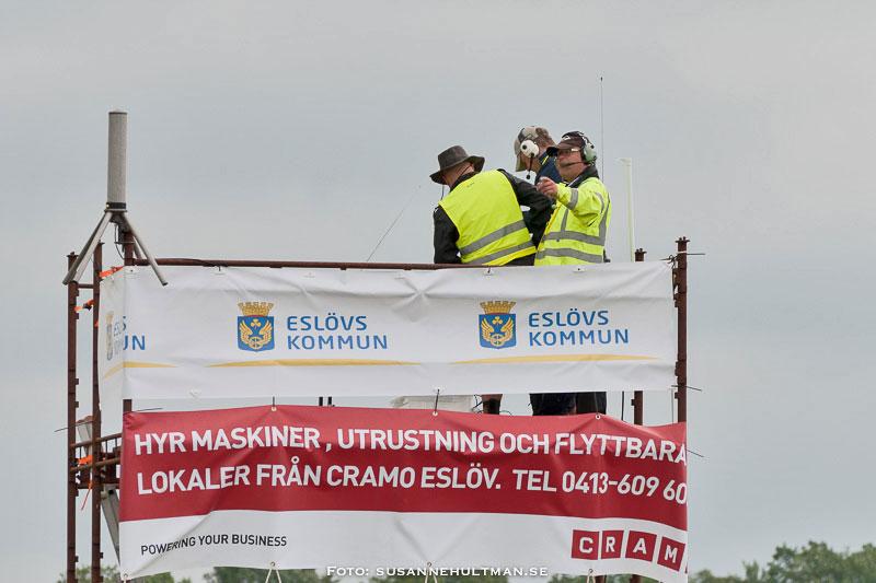 Män med gula västar i speakertorn med kommunens banderoller