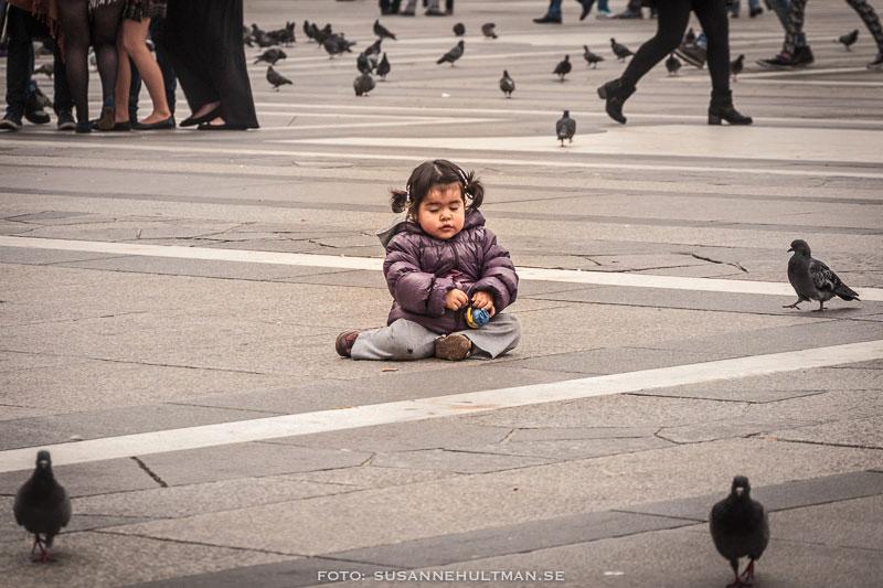 Ensam flicka omgiven av duvor