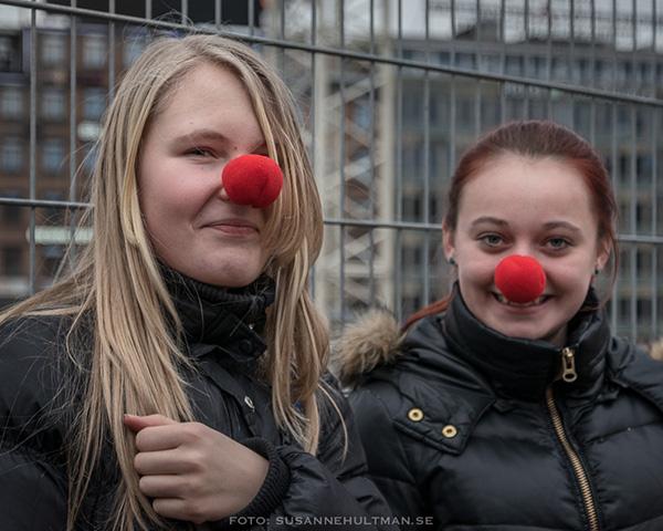 Två leende tjejer med röda clownnäsor