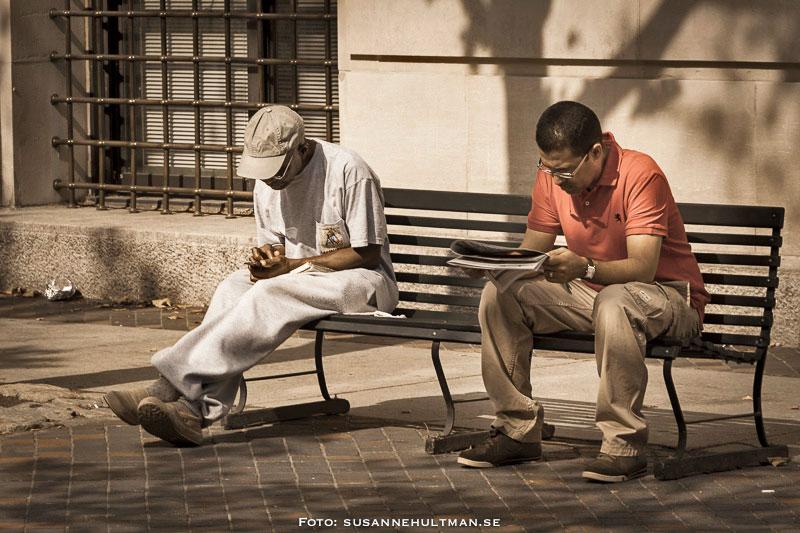Två män på en bänk. En är försjunken i en mobil och en i en tidning.