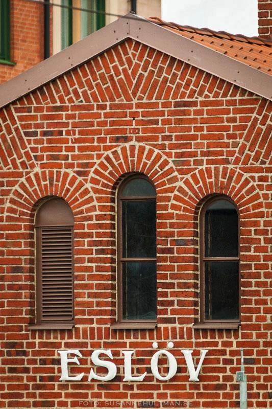 Eslövsskylt på tegelvägg med tre fönster