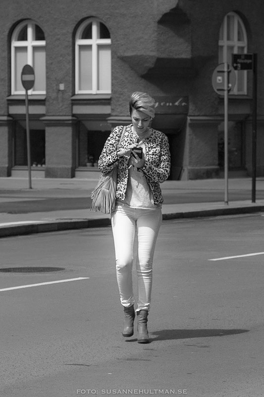 Kvinna korsar gatan fullt upptagen med sin mobil