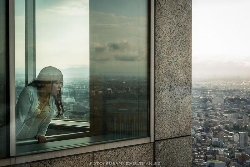 Flicka tittar ut från fönster