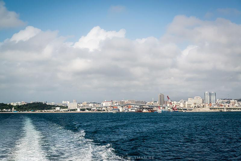 Vågor efter båten och Naha i bakgrunden