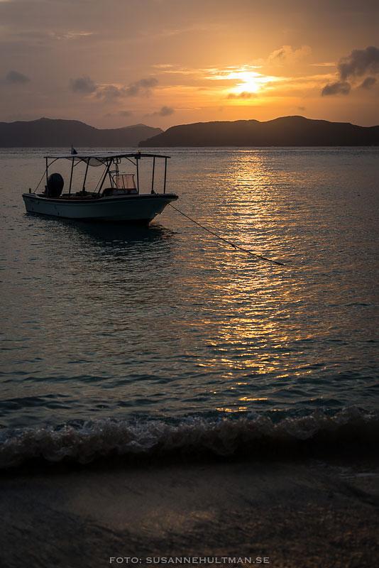 Båt i solnedgången och vågor mot strand.